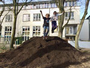 Kinder springen von Kompost-Haufen